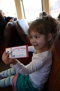 Coraline holds up her train ticket.